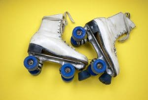 white skates with blue wheels on a yellow background