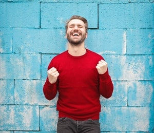 "Man smiling with ""YES!"" fists in front of wall"