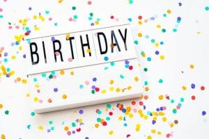 Birthday sign flatlay on white with colorful confetti