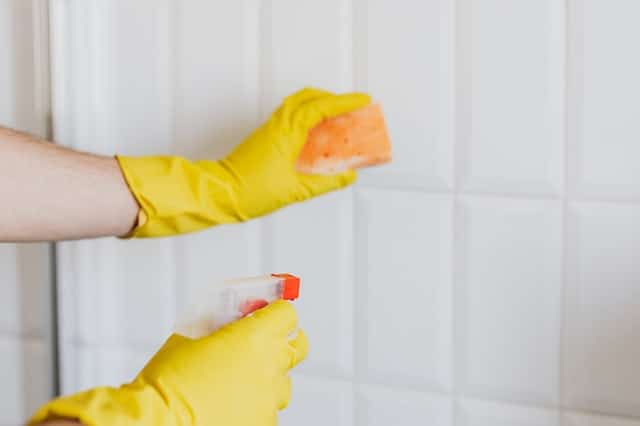 Cleaning tiles with yellow gloves and sponge