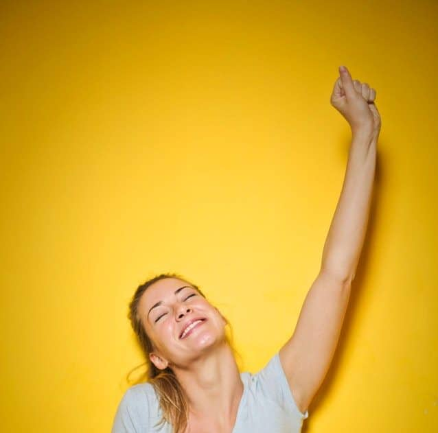 Happy woman with arm raised triumphantly in front of yellow wall