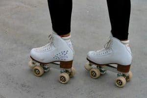 ankles down shot of girl wearing white quad skates decorated with marker