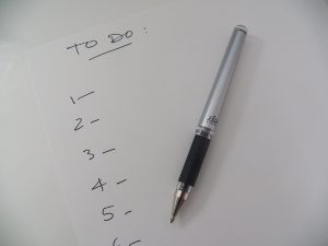 Handwritten to do list with numbers on a pad of paper with a pen sitting on top