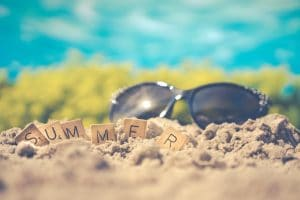 """""""Summer"""" spelled out in titles in front of sunglasses outside during summer"""
