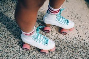 Close up shot of tan legs wearing white roller skates