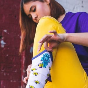Girl in colorful clothes putting on socks