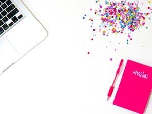 Overhead shot of white desk with laptop, planner, and confetti