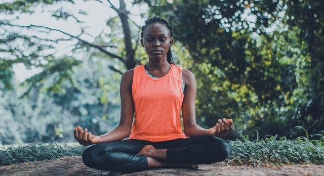 Woman in fitness clothes meditating outdoors