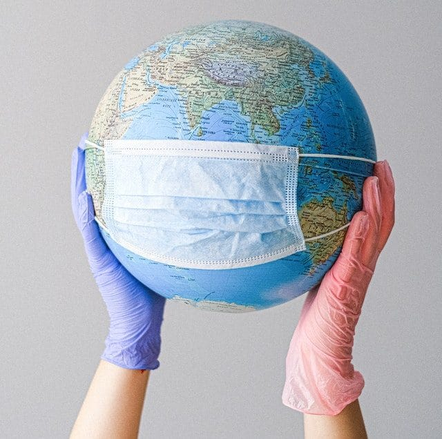 Hands in latex gloves holding globe with ppe mask