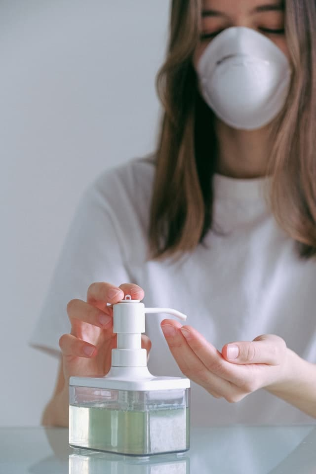 Young woman in ppe mask using hand sanitizer pump bottle