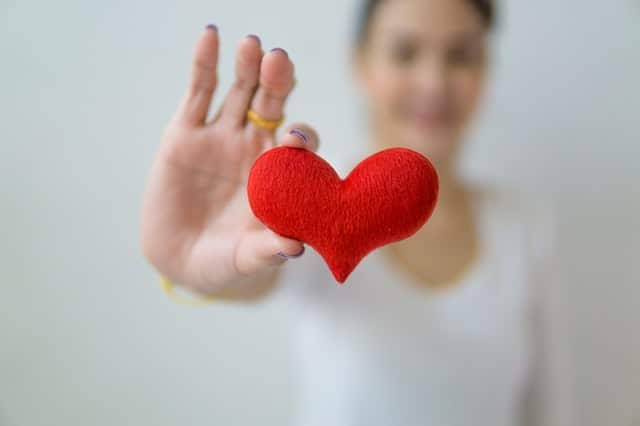 Woman holding red felt heart up to camera
