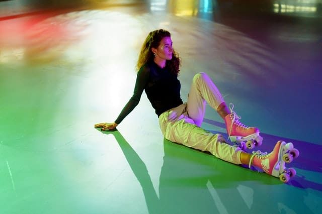Woman in pink quad skates lounging on floor amid colorful lights